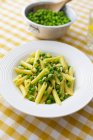 Penne with peas and pine nuts on plate — Stock Photo