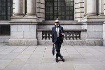 Reino Unido, Londres, retrato de un hombre de negocios elegante con gafas de sol y paraguas con traje y corbata - foto de stock