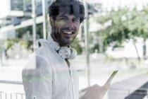 Porträt eines lächelnden jungen Mannes, der sein Handy hält und in die Kamera blickt — Stockfoto