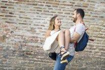 Щаслива людина з рюкзаком проведення подруга на цегляній стіні — стокове фото