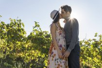 Italy, Tuscany, Siena, young couple kissing in a vineyard — Stock Photo