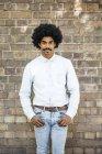 Homme afro-américain debout devant un mur de briques, les mains dans les poches — Photo de stock