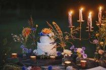 Torta nuziale a tavola con candele all'aperto — Foto stock