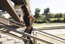 Mujer joven y deportiva corriendo por las escaleras - foto de stock