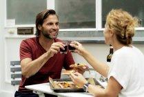 Счастливая пара сидит в саду, ест пиццу, пьет вино, тосты — стоковое фото