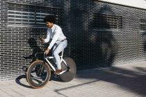 Афроамериканець людина їхав на велосипеді, використовуючи смартфон — стокове фото