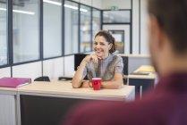 Женщина-работница, сидящая за столом и разговаривающая с коллегой — стоковое фото