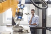 Businessman checking industrial robot in high tech company — Stock Photo