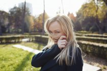 Portrait of playful blond woman in autumnal city park — Stock Photo