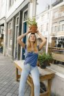 Netherlands, Maastricht, young woman balancing flowerpot on her head in the city — Stock Photo