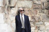 Portrait of senior businessman in blue suit listening music with headphones — Stock Photo