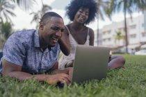 Etats-Unis, Floride, Miami Beach, jeune couple riant regardant ordinateur portable sur la pelouse dans un parc — Photo de stock