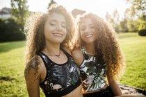 Портрет улыбающихся сестер-близнецов на подсветке — стоковое фото