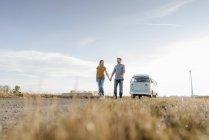 Молода пара ходьба на бруд трек на кемпер Ван в сільській місцевості — стокове фото