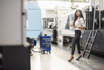 Woman with tablet at machine in factory shop floor looking around — Stock Photo