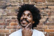 Uomo afroamericano in piedi davanti al muro di mattoni, guardando in alto, sorridendo — Foto stock