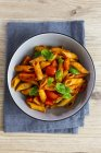 Top view of Penne with tomato and basil in bowl — Stock Photo