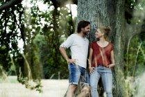 Счастливая пара, опираясь на дерево, улыбаясь друг другу — стоковое фото