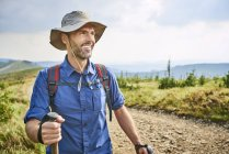 Portrait of smiling man hiking in the mountains — Stock Photo