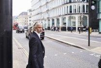Reino Unido, Londres, homem de negócios sênior que espera na Crosswalk na manhã — Fotografia de Stock
