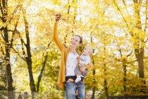 Mãe e bebê menina se divertindo com folhas no outono — Fotografia de Stock