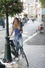 Pays-Bas, Maastricht, jeune femme à vélo dans la ville — Photo de stock