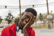 Portrait of a young black man, laughing with hand on his face — Stock Photo