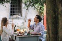 Casal ter uma refeição romântica à luz de velas e beber de copos de vinho — Fotografia de Stock