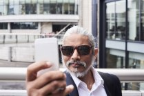 Portrait of grey-haired senior businessman taking selfie with smartphone — Stock Photo