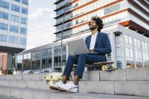 Spain, Barcelona, young businessman sitting outdoors in the city working on laptop — Stock Photo