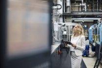 Женщина с планшетом на станке в цехе завода смотрит вокруг — стоковое фото