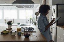 Mujer de pie en su cocina, usando tableta digital - foto de stock