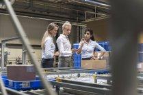 Три женщины обсуждают на конвейере на заводе — стоковое фото