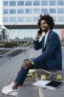 España, Barcelona, joven empresario sentado al aire libre en la ciudad y utilizando teléfono celular y portátil - foto de stock