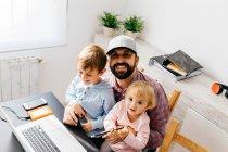 Padre trabajando en casa, usando laptop con sus hijos en su regazo. - foto de stock