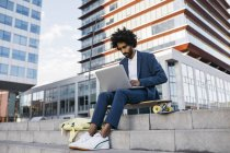 Spain, Barcelona, young businessman sitting outdoors in the city and working on laptop — Stock Photo