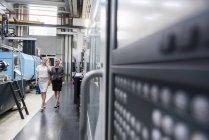Две женщины с планшетом ходят и разговаривают в цехе завода — стоковое фото