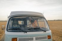 Happy young woman driving camper van in rural landscape — Stock Photo