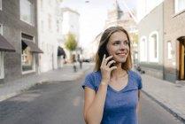 Pays-Bas, Maastricht, jeune femme souriante sur téléphone portable dans la ville — Photo de stock