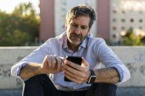 Homem maduro sentado na cidade e usando telefone celular — Fotografia de Stock