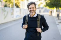 Portrait of smiling mature man wearing a backpack in the city — Stock Photo