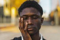Joven negro con los ojos cerrados y la mano en la cara - foto de stock