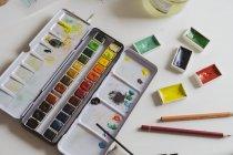 Aquarelas e lápis de cor na mesa de trabalho — Fotografia de Stock