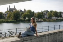 Netherlands, Maastricht, young woman sitting on a wall at the riverside with laptop — стоковое фото
