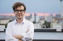 Alemanha, Berlim, retrato do empresário bem sucedido no terraço do telhado ao pôr-do-sol — Fotografia de Stock