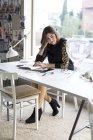 Junge Designerin schaut Buch in ihrem Atelier — Stockfoto