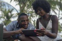 Junge Frau zeigt Tablet zu Freund in einem Park — Stockfoto