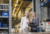 Две женщины с планшетом разговаривают на фабричном складе — стоковое фото