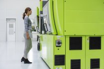 Businesswoman in high tech company controlling manufacturing machines — Stock Photo