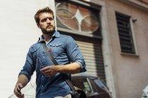 Портрет бізнесмена з використанням смартфонів і навушниками на відкритому повітрі — стокове фото